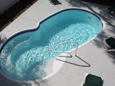 Sparkling 12x23 salt-chlorinated pool with privacy fence, lounge chairs