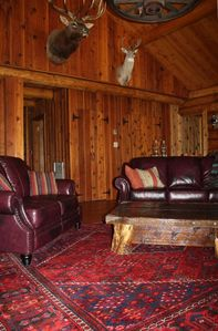 Large living room with vaulted ceilings, leather sofas, lodge style decor.