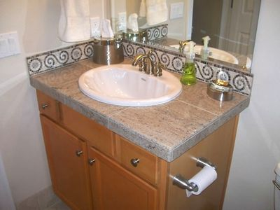 Custom bathrooms with granite countertops, tile floors.