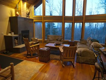 Family style greatroom with wood burning fireplace and a view of the forest.