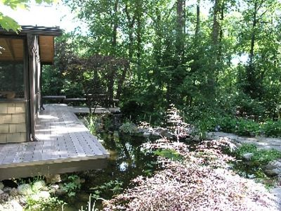 ZENADU: CHICAGO CHIC MEETS WOODLAND RUSTIC IN THIS TRANQUIL RETREAT - Deck overhangs pond with floating lilies