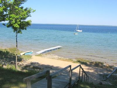 Suttons Bay house rental - View of sandy beach, dock, stairs, canoe, kayak, and firepit with large log