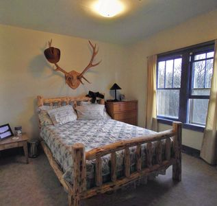Laramie's bedroom has a solid heavy log queen bed and rustic decor.