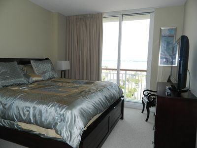 The second bedroom has a king size bed, a flat screen TV and view of the sound