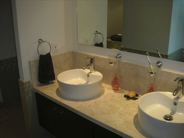 Dual sinks in ensuite master bathroom with marble countertops