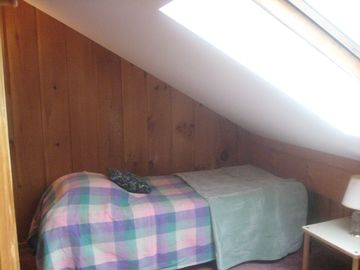 The second twin bed in the loft with skylight.