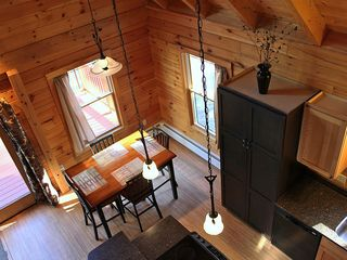 Harrison cabin photo - View from loft stairs--table expands to hold 8 dinner guests