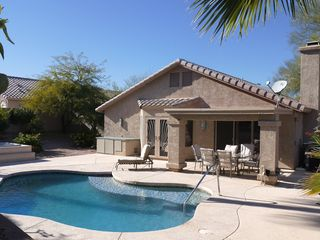 Fountain Hills house photo - Backyard with Playpool and heated Spa surrounded by palm trees and citrus tree