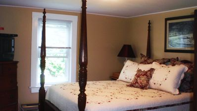 Spacious second master bedroom with queen size bed and television.