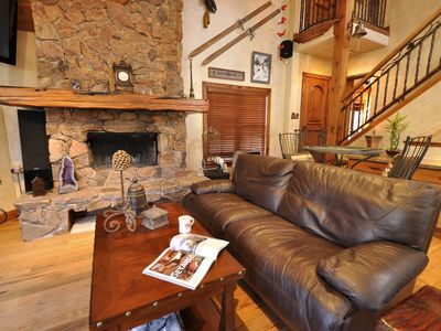 "Spacious living room with 60"" Flat Screen Television. Wood burning fireplace."