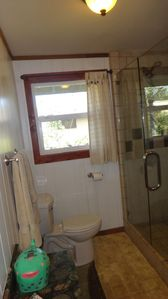 Full bathroom in the Hallway with walking shower with glass door,granit counter.