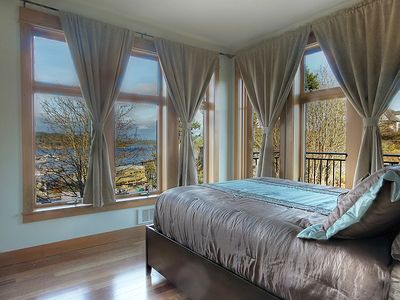 Master bedroom is furnished with a queen bed and has harbor views