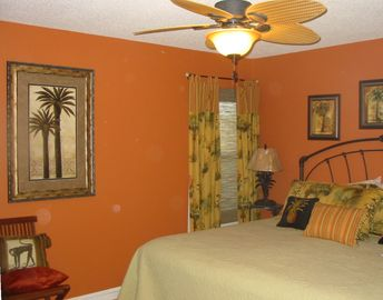 The master is a tropical retreat with a king bed under a large ceiling fan.