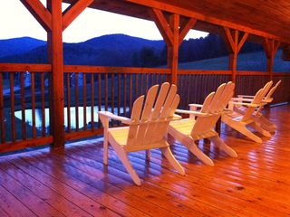 Gorgeous wrap-around porch with relaxing adirondack chairs.