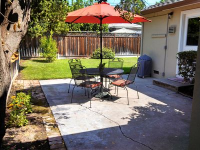 Patio area of backyard with umbrella table and Weber BBQ for your use.