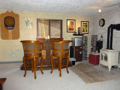 Another view of the lower level den with a small bar area and soft tip dartboard