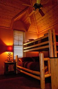 Guest bedroom has bunk beds with a double bed on the bottom and a twin bed on to