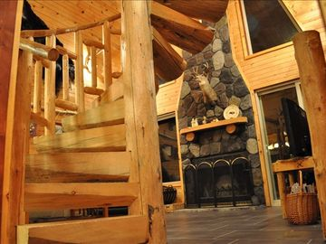 Lead cabin rental - Spiral staircase to upper loft bedroom and view of fireplace/hearth.