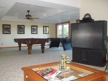 Basement recreation room with pool table ,air hockey table, and TV visible