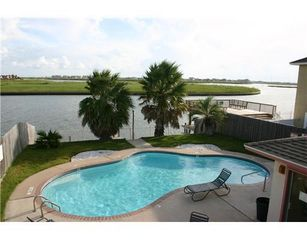 Swim in outdoor pool located on canal. Fishing pier right below the palm trees. - Corpus Christi condo vacation rental photo
