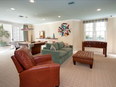 Lower level playroom (large screen TV  not visible); patio leads to pool deck.