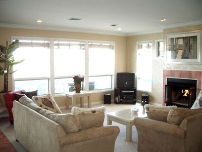 Spacious Living Room with Gas Fireplace & Wall of Windows facing the Beach