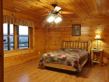 Lower bedroom w/ queen log bed. 1 of 3 bedrooms with a single queen log bed.