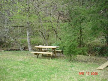 Picknic table, benches, and fire pit down by the creek