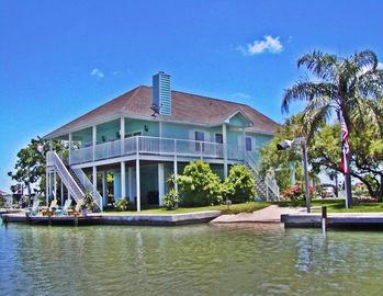 Rockport house rental - Side view showing stairway to entrances and private lighted fishing dock and boat ramp.