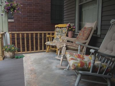 Covered porch with rockers overlooking back yard
