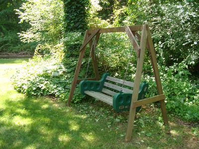 Swing for two in the lush back yard woodlands setting.
