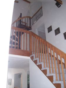 Stairway to second floor and view of spiral stairway to loft.