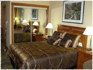 Queen size bed in the bedroom suite. The suite contains a private bath.