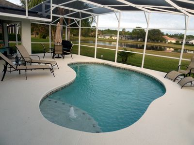 Heated pool under screened lanai featuring grill and 16 piece patio set