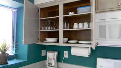 Cabinets are clean and organized with place settings for 8. Wineglasses too!
