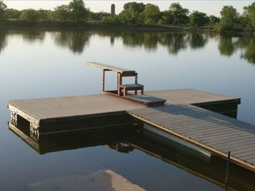 The dock has been rebuilt and put back in place. About 15' deep at end of board.