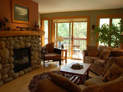 Canmore condo rental - Cozy living room with river rock gas fireplace and log mantle.
