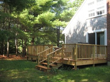 Deck has large picnic table with sun umbrella and plenty of chairs.