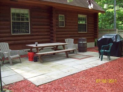 Backyard patio with grill, picnic table and other furniture.