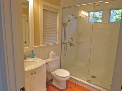 There is a full bath off the kitchen with an over-sized tile and glass shower