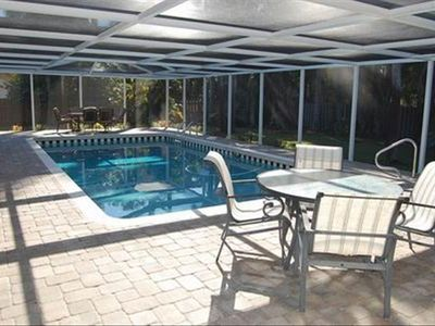 Sparking pool with screened lanai and outdoor dinings spaces