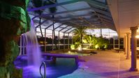 Water-park style pool with hot tub in grotto w. waterfall + bridge over pool