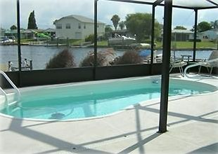 Your heated screened in pool, out your back door and steps from the water