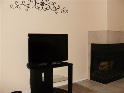 Living room with a wood-burning fire place, flat screen TV and DVD player.
