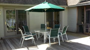 Wrap around deck with dining for six and lighted umbrella