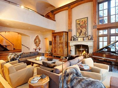 Living room with enormous wood burning fireplace and vaulted ceilings
