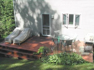 Back deck with outdoor lounges, table chairs and gas grill.
