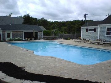 Pool looking onto patio,gate,and pool house