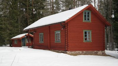 Red log cabin in the relaxing environment with opportunities for activities