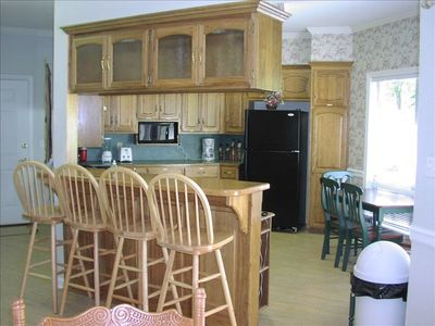 Kitchen area with bar, breakfast table and all appliances
